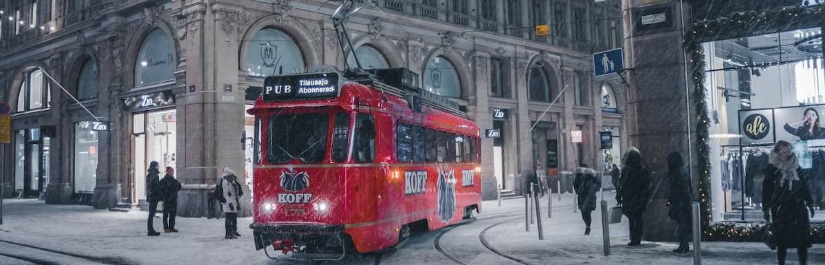 How You Can Study In Finland Tuition-Free This Year. Red tram on snowy night in Helsinki.